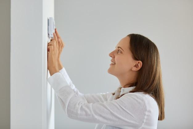 밝은 방, 스마트 홈의 흰색 벽에 온도 조절기가 있는 난방 온도를 조절하는 흰색 셔츠를 입고 웃고 있는 검은 머리 여성의 측면 초상화.