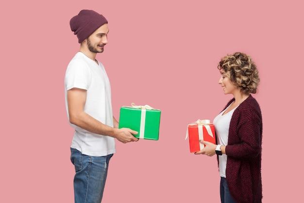 캐주얼한 스타일로 서 있는 놀란 두 친구의 옆모습 초상화, 서로에게 선물 상자를 주고, 기념일을 축하하고, 이빨 미소. 절연, 실내, 스튜디오 촬영, 분홍색 배경