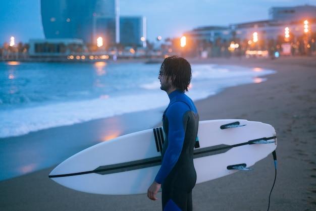 サーフィンの準備ができてサーフボードを持って立っているサーファーの側面図の肖像画