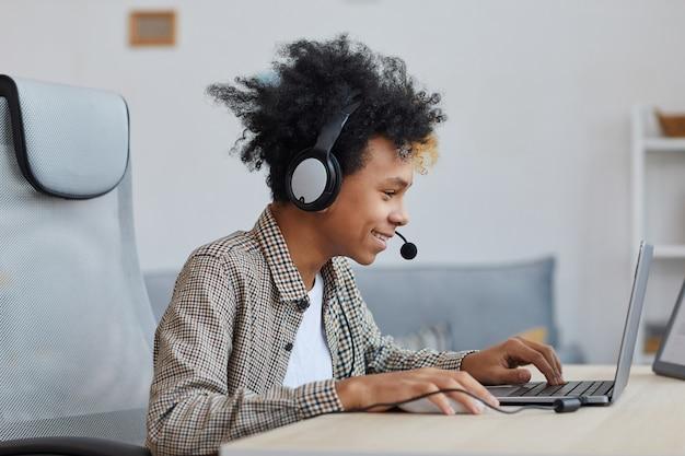 自宅でビデオゲームをプレイし、嬉しそうに笑っている10代のアフリカ系アメリカ人の少年、若いゲーマーまたはブロガーのコンセプト、コピースペースの側面図の肖像画