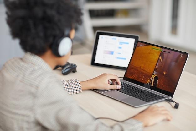 ラップトップ、コピースペースを介してオンラインでビデオゲームをプレイしている10代のアフリカ系アメリカ人の少年の側面図の肖像画