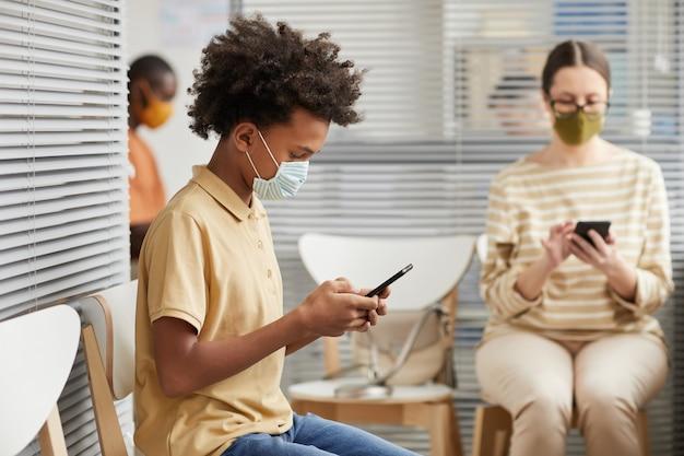 Портрет молодого афроамериканского мальчика-подростка, использующего смартфон или играющего в мобильные игры, в очереди в медицинской клинике, вид сбоку