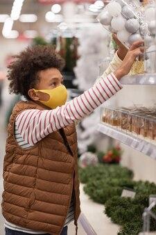 一番上の棚のクリスマスの装飾に到達しながらスーパーマーケットでマスクを身に着けている10代のアフリカ系アメリカ人の少年の側面図の肖像画