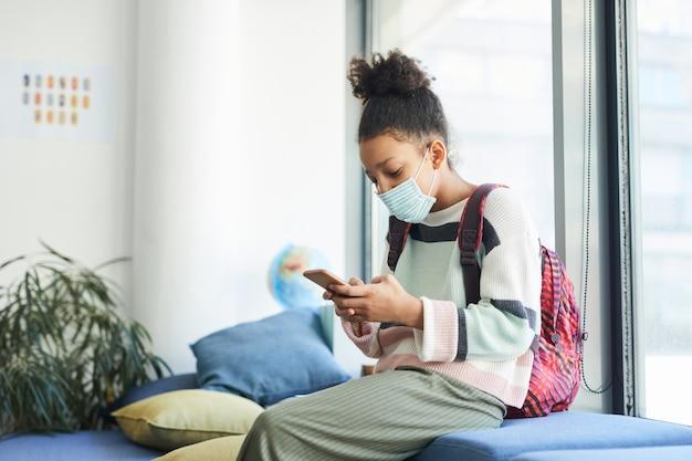 学校の教室でマスクを着用し、スマートフォンを見ている10代のアフリカ系アメリカ人の女の子の側面図の肖像画、covid安全対策