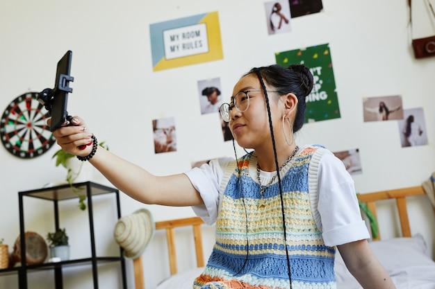 Портрет модной девочки-подростка, держащей смартфон во время записи видео или потоковой передачи в уютной комнате, вид сбоку