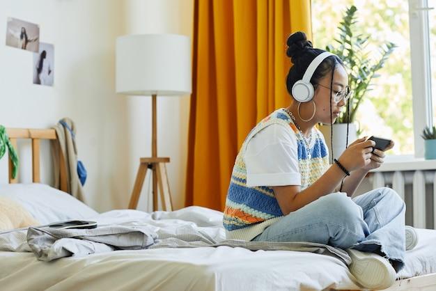 Вид сбоку портрет модной девочки-подростка, играющей на смартфоне в мобильную игру vi, сидя на кровати в уютной комнате, копией пространства