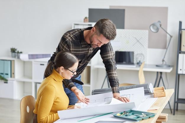 사무실에서 함께 작업하는 동안 청사진에 협력하는 두 건축가의 측면보기 초상화,