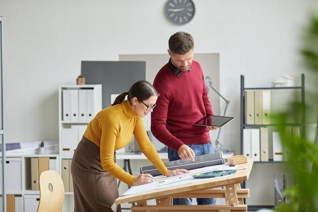 사무실에서 함께 작업하는 동안 청사진을 그리는 두 건축가의 측면보기 초상화,
