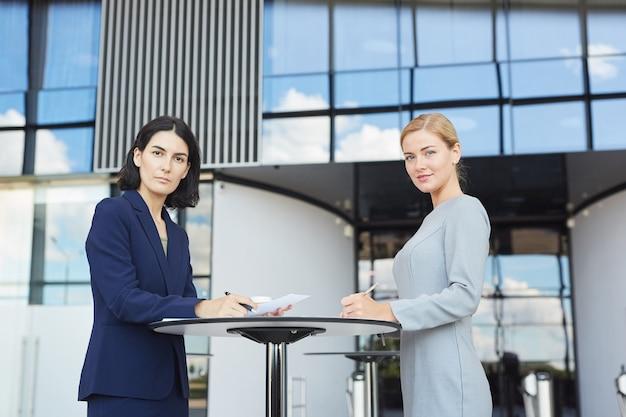 Портрет двух деловых женщин, улыбающихся в камеру, стоя у столика в кафе в аэропорту или офисном здании, вид сбоку,