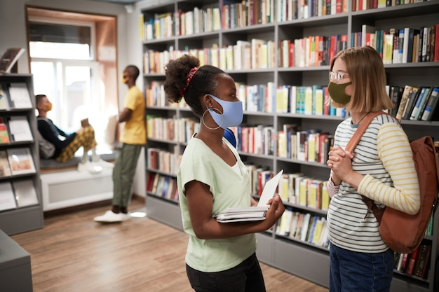 Портрет двух студенток в масках во время беседы в копировальном пространстве школьной библиотеки, вид сбоку