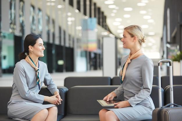 Портрет двух бортпроводников, сидящих на диване в зале ожидания аэропорта и смотрящих друг на друга, вид сбоку,
