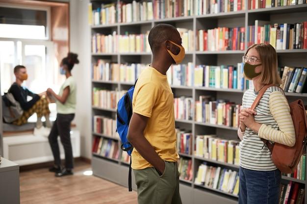 Портрет двух учеников в масках во время беседы в копировальном пространстве школьной библиотеки, вид сбоку