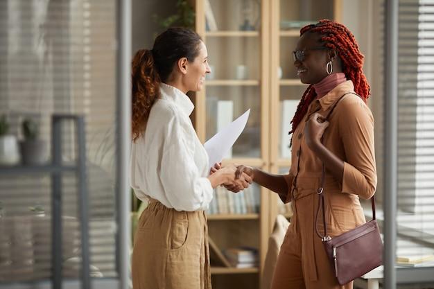 Портрет вид сбоку двух успешных молодых женщин, пожимающих руки и весело улыбаясь, стоя в современном офисном интерьере, копией пространства
