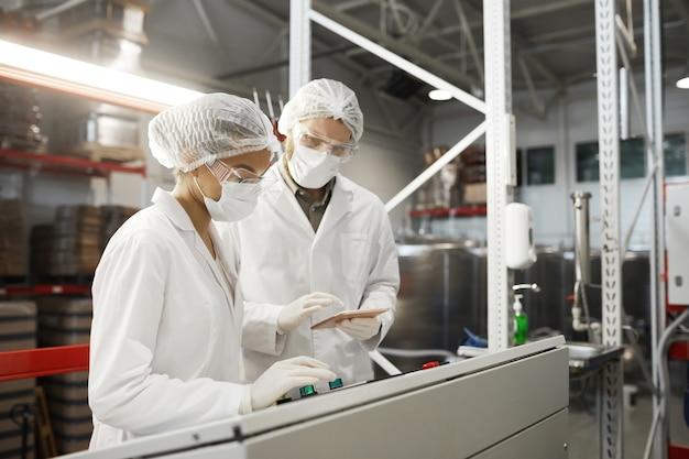 化学プラント、コピースペースで機械ユニットを操作しているときに保護服を着ている2人の労働者の側面図の肖像画