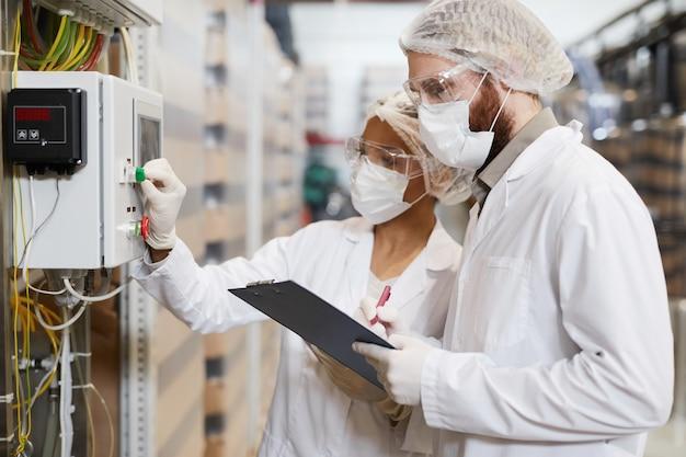 化学プラントで機械を操作しているときに防護服を着ている2人の労働者の側面図、コピースペース