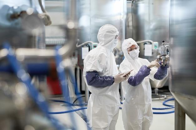 현대 화학 공장에서 장비를 사용하는 동안 보호복을 입은 두 작업자의 측면 초상화, 복사 공간