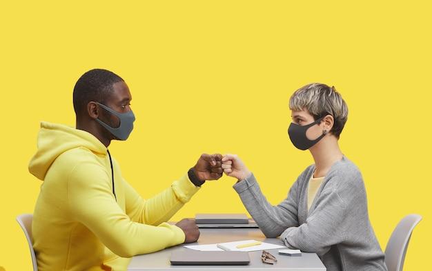 黄色の背景との出会いの間に机に向かい合って座っている間、マスクを着用し、拳をぶつける2人の若いビジネスマンの側面図の肖像画
