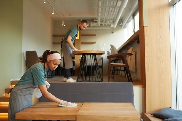 따뜻한 나무 액센트가 있는 커피숍에서 테이블을 청소하는 두 젊은 웨이터의 측면 초상화, 복사 공간