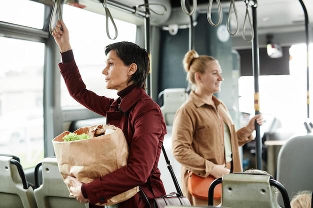 Вид сбоку портрет женщины, держащей сумку с продуктами в автобусе во время поездки на общественном транспорте и держащейся за перила, копией пространства
