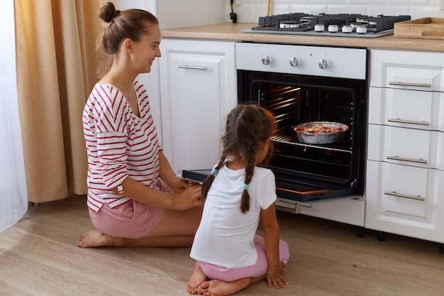 Вид сбоку портрет женщины в полосатой повседневной рубашке и ее дочери в белой футболке, сидящей на полу на кухне и ожидающей готовности выпечки.
