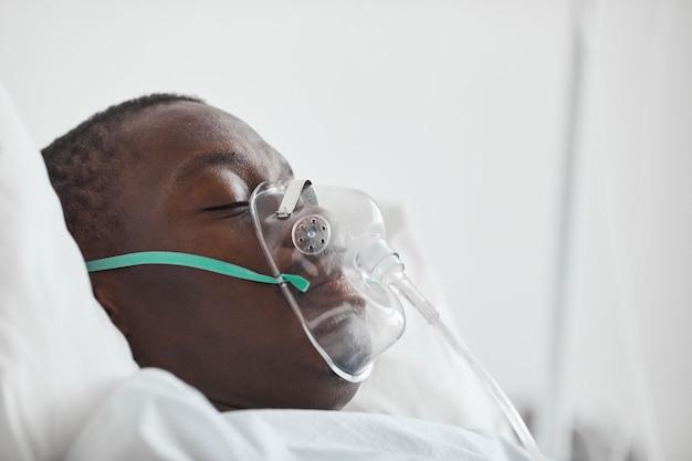 酸素マスク、コピースペースと病院のベッドで若いアフリカ系アメリカ人男性の側面図の肖像画