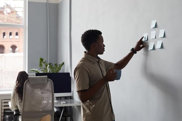 オフィスでプロジェクトを計画している間、壁にステッカーのメモを置く若いアフリカ系アメリカ人男性の側面図の肖像画、コピースペース