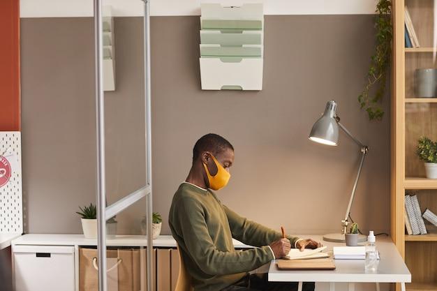 オフィスのキュービクル、コピースペースのデスクで作業中にマスクを着用し、プランナーで書いている若いアフリカ系アメリカ人男性の側面図の肖像画