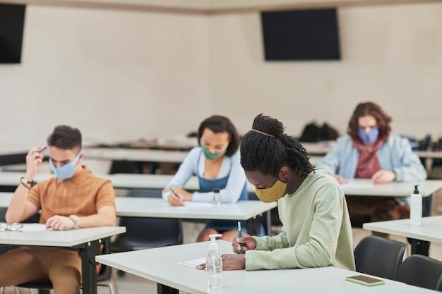 多様な人々のグループ、コピースペースで学校でテストや試験を受けている間マスクを身に着けている若いアフリカ系アメリカ人男性の側面図の肖像画
