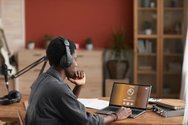 집 녹음 스튜디오에서 음악을 작곡하는 동안 헤드폰을 착용하는 젊은 아프리카 계 미국인 음악가의 측면보기 초상화, 복사 공간