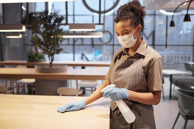 ショッピングモール、コピースペースのフードコートでテーブルを掃除する若いアフリカ系アメリカ人女性の側面図の肖像画