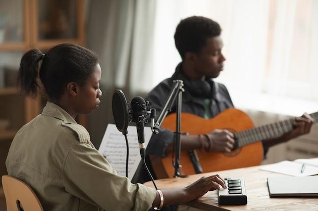 Портрет молодой афро-американской женщины, играющей на клавишных во время написания музыки в домашней студии звукозаписи, вид сбоку