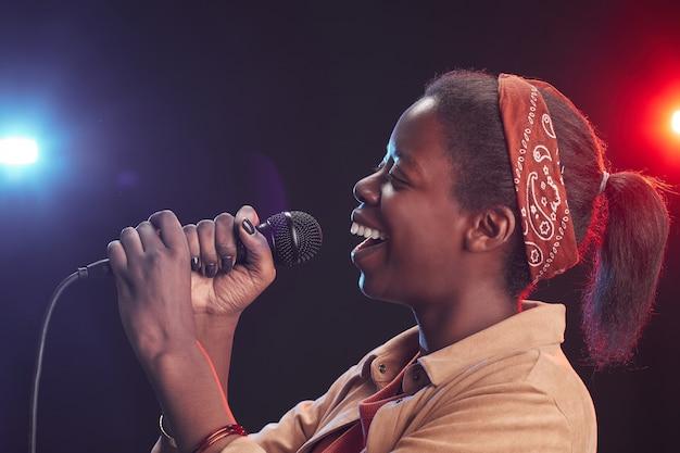 Портрет молодой афро-американской женщины, поющей в микрофон, стоя на сцене, вид сбоку