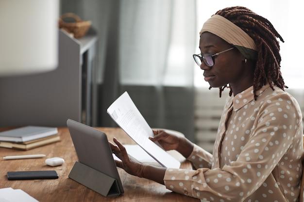 Вид сбоку портрет молодой афро-американской женщины в очках и с помощью цифрового планшета на подставке во время работы из дома, копией пространства