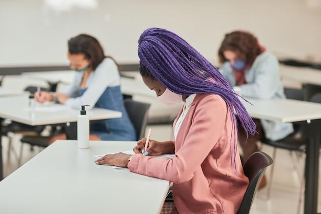 多様な人々のグループ、コピースペースで学校でテストや試験を受けている間マスクを身に着けている若いアフリカ系アメリカ人女性の側面図の肖像画