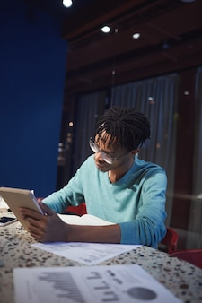 Портрет молодого африканского бизнесмена, работающего допоздна, сидя за столом в темной комнате и используя цифровой планшет, вид сбоку
