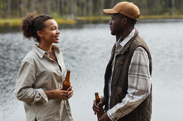湖のそばに立っている間屋外でチャットする若いアフリカ系アメリカ人のカップルの側面図の肖像画