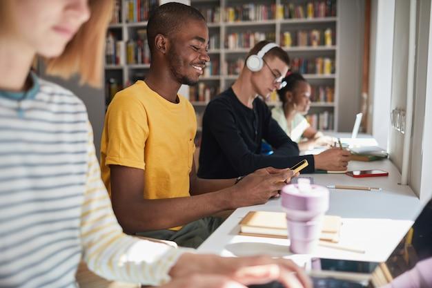 Портрет молодого афроамериканца, занимающегося с группой студентов в школьной библиотеке, вид сбоку ...