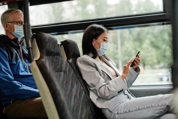 버스에서 마스크를 쓰고 도시에서 통근하는 동안 스마트폰을 사용하는 젊은 아시아 여성의 측면 초상화, 복사 공간