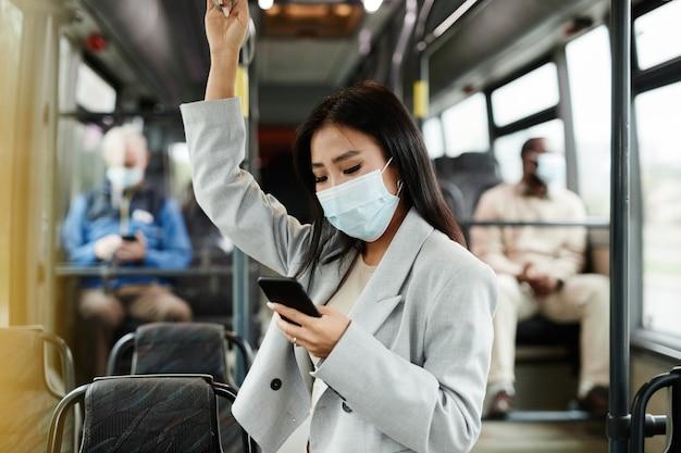 Вид сбоку портрет молодой азиатской женщины в маске в автобусе и использования смартфона во время поездок по городу