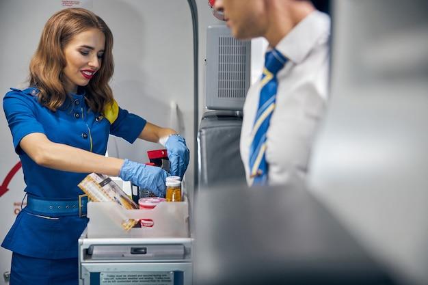 승객 일등석 및 비즈니스 클래스를 위해 비행기에서 식사를 제공하는 젊은 항공 직원의 측면보기 초상화