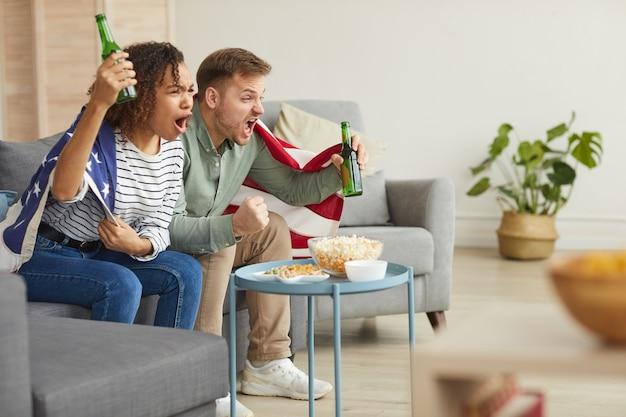 Портрет молодой пары, смотрящей на спортивный матч по телевизору дома и эмоционально аплодирующей, нося американский флаг