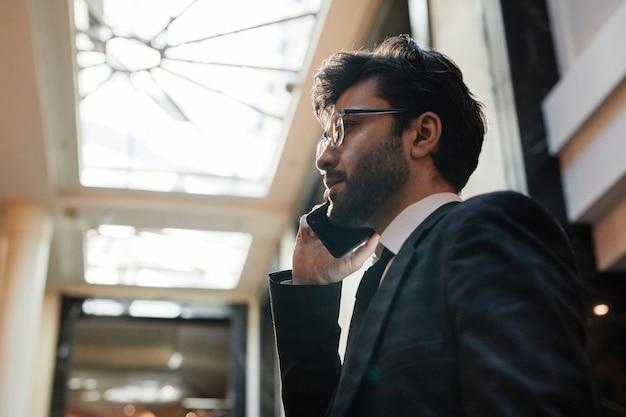 출장 중 호텔 로비에서 스마트폰으로 말하는 젊은 중동 사업가의 측면 초상화, 복사 공간