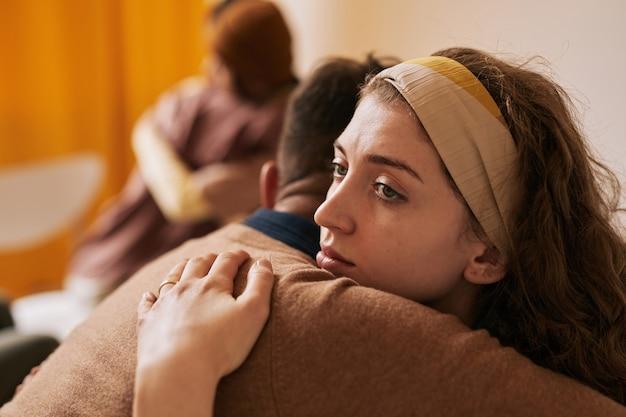 지원 그룹, 복사 공간에서 치료 세션 동안 남자를 껴안은 젊은 여성의 측면보기 초상화