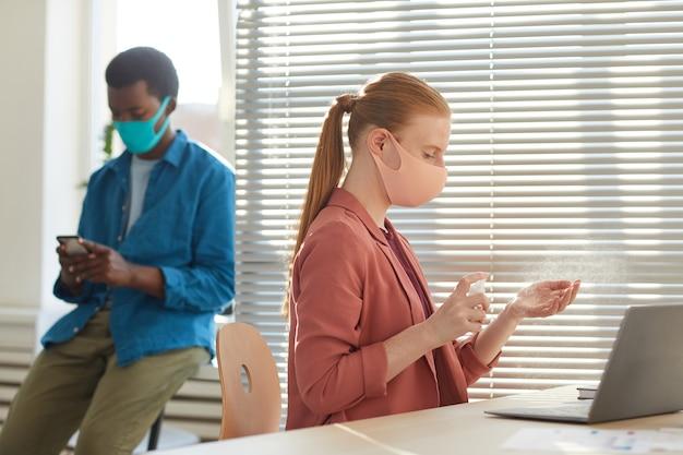 Портрет молодой женщины в маске, дезинфицирующей руки на рабочем месте в офисе после пандемии, вид сбоку