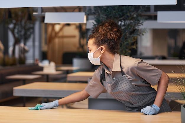 モダンなレストランのインテリア、covid安全コンセプト、コピースペースでテーブルを掃除しながらマスクを身に着けている若い女性の側面図の肖像画
