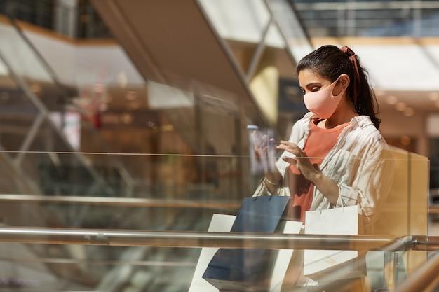 Вид сбоку портрет молодой женщины в маске во время покупок в торговом центре и с использованием смартфона, копией пространства