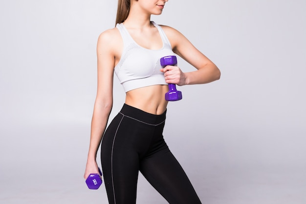 Side view portrait of a pretty young sportswoman doing exercises with dumbbells isolated on a white wall