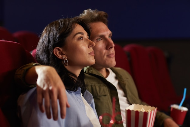 Side view portrait of romantic young couple watching movie in cinema, focus on woman looking up and holding popcorn, copy space