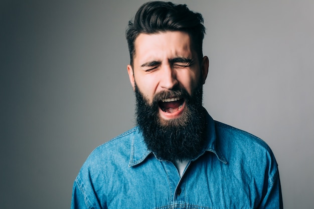 Side view portrait of screaming bearded man - gray wall
