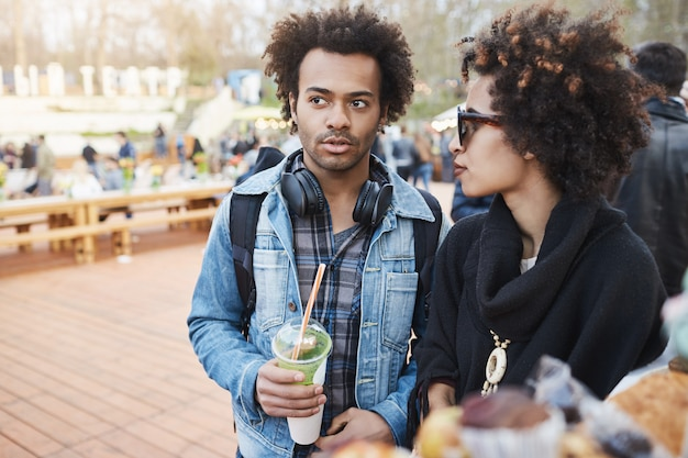 Side-view portrait of serious attractive dark-skinned boyfriend with afro hairstyle walking on food festival with girlfriend, drinking coffee and talking